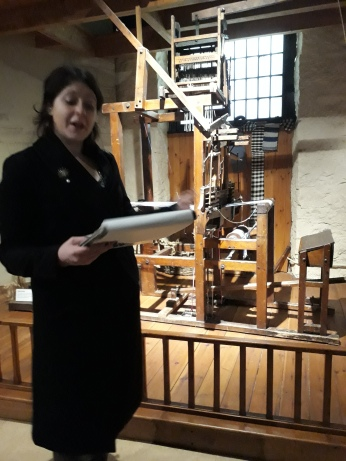 Erin reading before a hand loom